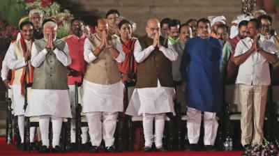 Indian Prime Minister Narendra Modi, (left) with his newly sworn cabinet ministers greet the invitees at the end of the swearing-in ceremony at the forecourt of presidential palace in New Delhi. (Photo: AP)