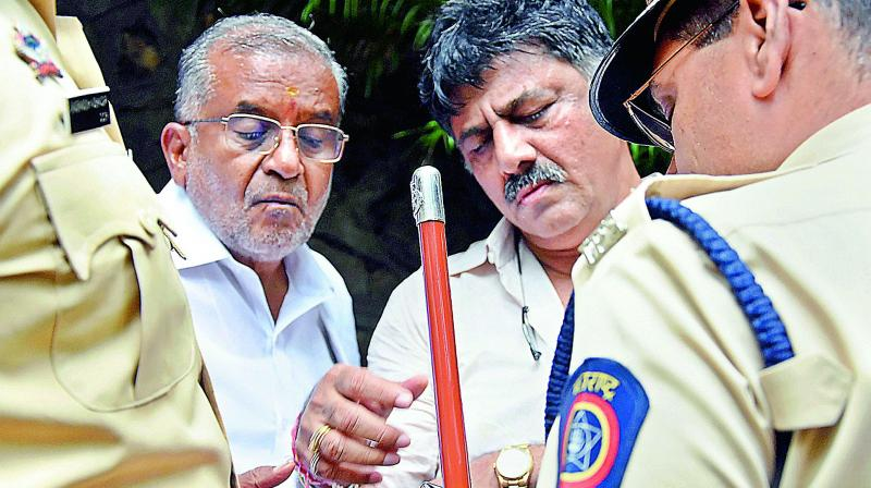 Karnataka ministers G.T. Devegowda and D.K. Shivakumar interact with the police personnel at Hotel Renaissance, where the 10 rebel MLAs are staying, in Mumbai, on Wednesday.   (PTI)