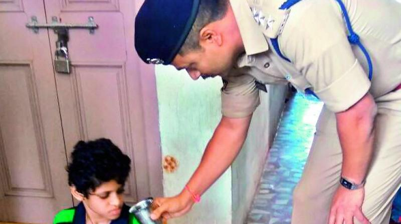 ACP Chaitanya Kumar offers a glass of water to the boy outside his home.