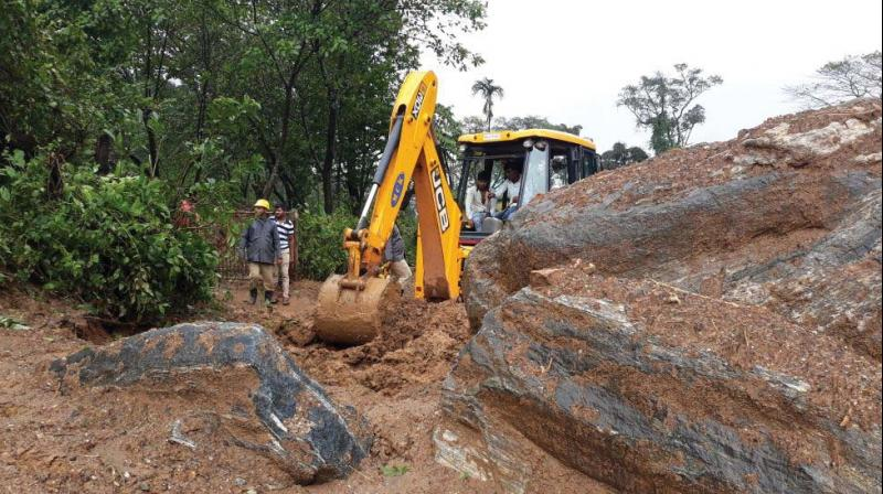An earth-mover clears the sludge from a road in the flood-hit in Mangaluru (Image: DC)