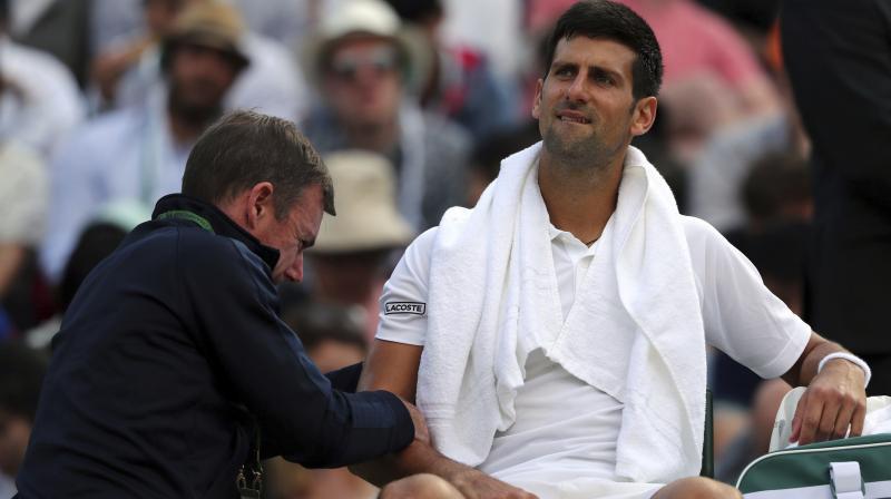 Novak Djokovic receives medical treatment during his Men's Singles Match against Czech Republic's Tomas Berdych on day nine of the Wimbledon Tennis Championships. (Photo: AP)