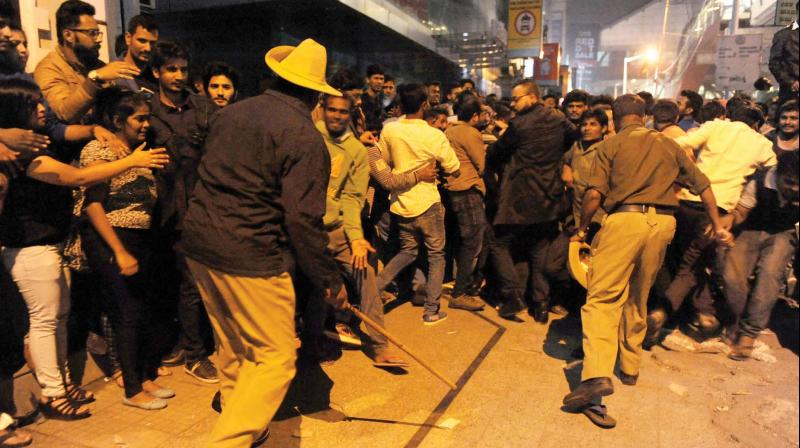 Policemen cane revellers who gathered at MG Road and Brigade Road to celebrate New Year (Photo: DC)