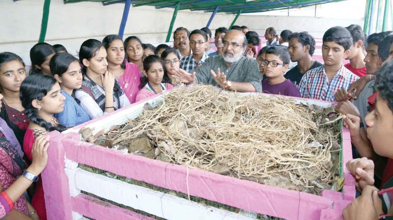 Finance minister Thomas Isaac explains to students on aerobic bins. (File pic)