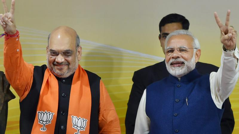 Prime Minister Narendra Modi and BJP President Amit Shah flash victory sign at a felicitation function before the party's parliamentary board meeting in New Delhi on Monday, after the party's win in Gujarat and Himachal Pradesh Assembly elections. (Photo: PTI)