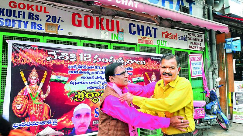 Mr Rahman, who was injured in the blast, and Mr J.N. Sharma, whose daughter died, hug each other at the Gokul chat bhandar. (Photo: P.Surendra)