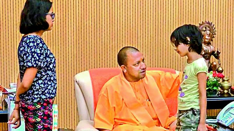 UP CM Yogi Adityanath interacts with Tiwari's family. —PTI