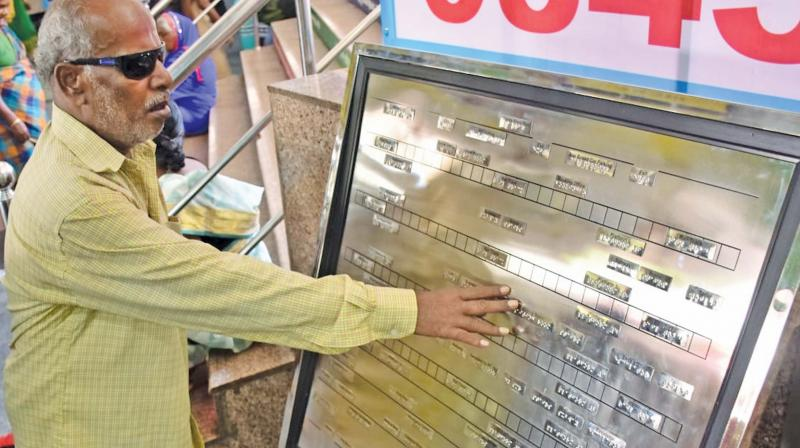 A visually impaired passenger tries the newly installed Braille board at Coimbatore junction entrance on Tuesday (Photo: DC)