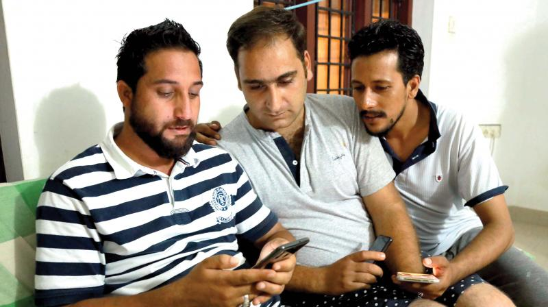 Wani Nisar, Ishfaq Ahammed Malik and Inayat Farooq from Kashmir watch news on the situation of Kashmir on their mobile phones in Mattancherry on Monday.(Photo:  ARUN CHANDRABOSE)