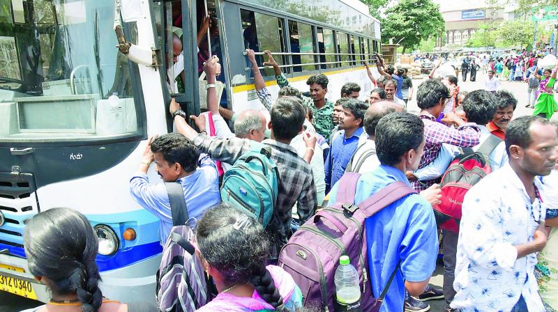 Passengers jostle to board a bus to reach their native places, at the Dwaraka bus station in Visakhapatnam on Wednesday.  (P. narasimha Murthy)