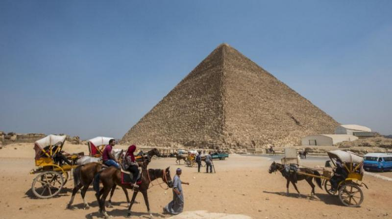 Egyptians ride their carts past the Great Pyramid of Cheops, aka Pyramid of Khufu, on August 31, 2016 on the Giza Plateau. (Photo: AFP)