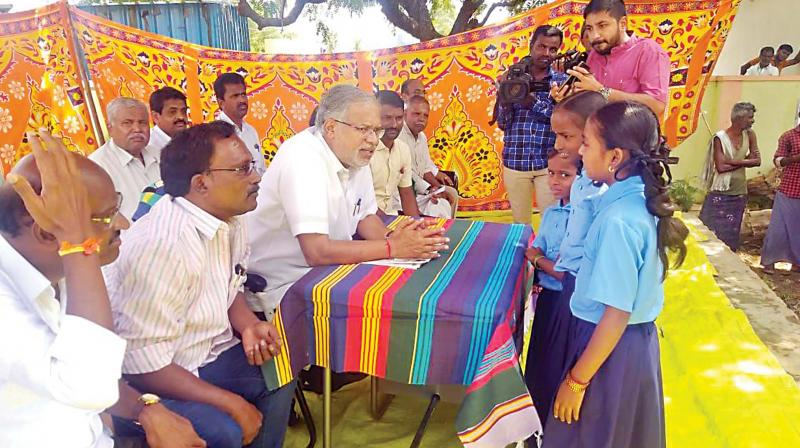 Minister for Primary and Secondary Education S. Suresh Kumar interacts with students of a government school at N. Achammanahalli village in Tumakuru on Friday (Photo: DC)