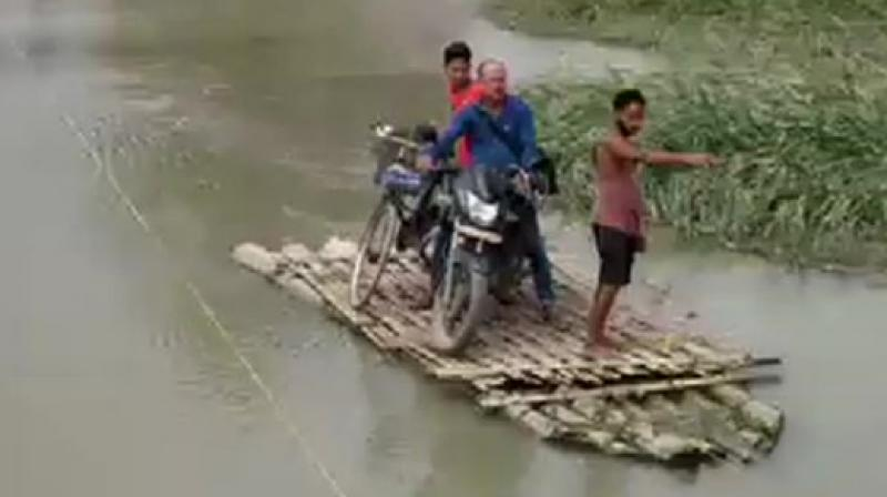 As heavy rainfall in Bhutan leads to rise in water levels of Pagladia and Borolia rivers washing away a bridge in Tamulpur & obstructing Tamulpur's connection to Baksa District Headquarters. (Photo: ANI)