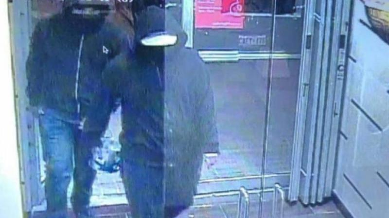 Police posted a photograph on Twitter showing two people with dark zip-up hoodies walking into an establishment with one of them appearing to be carrying an object. (Photo | Peel Regional Police Twitter)