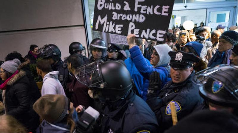 Protesters are surrounded by police officers and travelers as they pass through an exit of Terminal 4 at John F. Kennedy International Airport in New York. (Photo: AP)