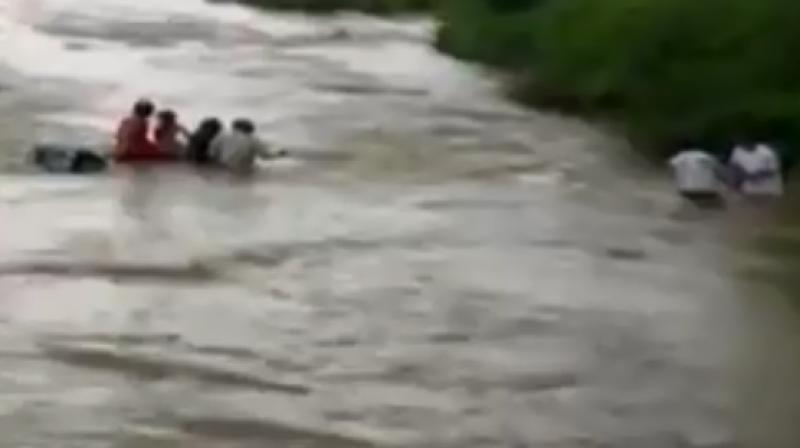 Ashraf Khalil Shaikh, his wife Hamida and two children were safely rescued by local villagers before the car could be washed away. (Photo: ANI/screengrab)