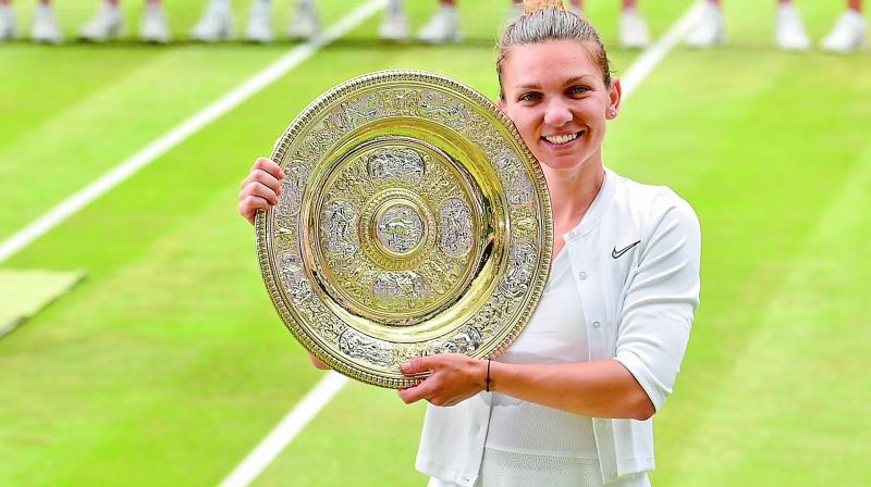 Simona Halep poses with the Venus Rosewater Dish trophy after winning the Wimbledon final.