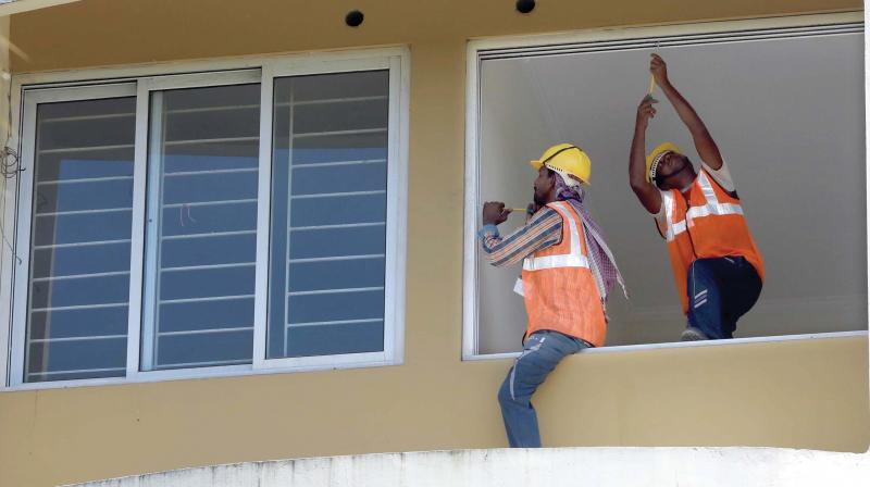 Workers of companies entrusted with the demolition work remove windows at Alfa Serene apartment in Maradu, Kochi, on Saturday. (Photo: ARUN CHANDRABOSE)