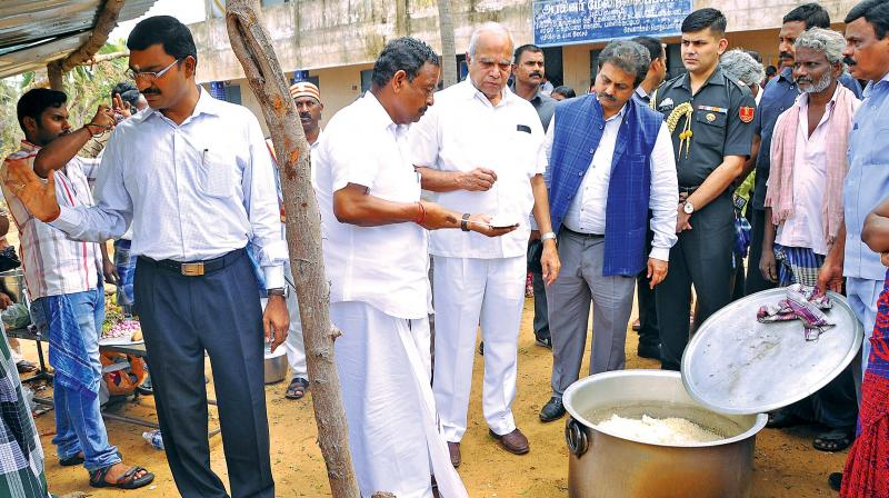 Governor Banwarilal Purohit and minister for handlooms and textiles O.S.Manian inspect rice cooked at a camp in Nagapattinam on Wednesday. (Photo: DC)