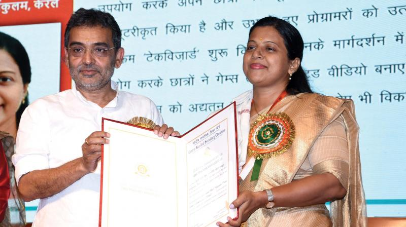 Union Minister of State for HRD Upendra Kushwaha presents the CBSE Teacher Award to Suma Paul in New Delhi.