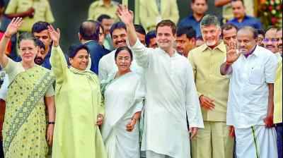 Newly sworn-in Karnataka Chief Minister H.D. Kumaraswamy along with Andhra Pradesh Chief Minister N. Chandrababu Naidu, AICC president Rahul Gandhi, West Bengal CM Mamata Banerjee, BSP leader Mayawati and Congress leader Sonia Gandhi wave after the swearing-in ceremony, in Bengaluru, on Wednesday. (Image: PTI)