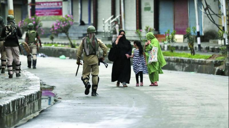 Kashmiris walk past paramilitary troops patrolling a street in Srinagar on Saturday. (Photo: AP)