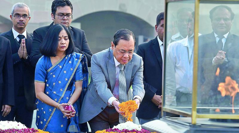 Outgoing Chief Justice of India Justice Ranjan Gogoi with wife Rupanjali pays homage at the samadhi of Mahatma Gandhi at Rajghat in New Delhi on Friday. (Photo: PTI)