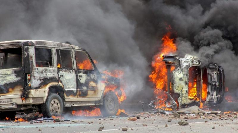Flames rise from a burning vehicle as Maratha Kranti Morcha protesters clashed with police personnel during a protest called for reservations in jobs and education in Navi Mumbai on July 25 2018. (Photo: PTI)