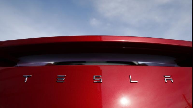 The sun shines off the rear deck of a roadster on a Tesla dealer's lot in the south Denver suburb of Littleton, Colo. (AP Photo/David Zalubowski, File)