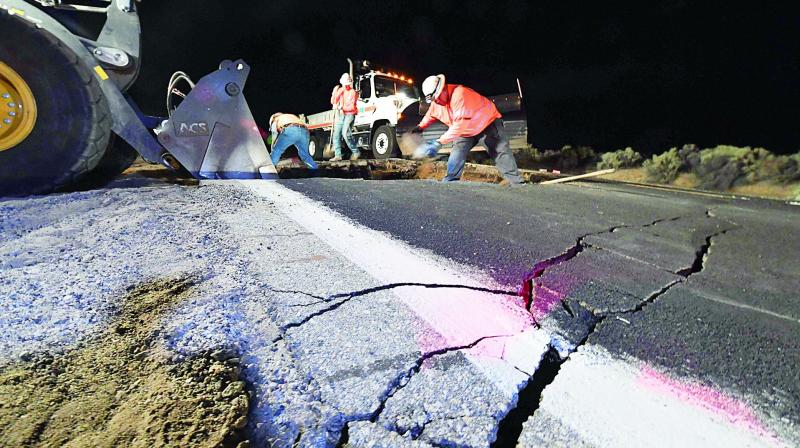 Highway workers repair a hole that opened in the road as a result of Friday's earthquake, near Ridgecrest, California, early in the morning on Saturday. — AFP