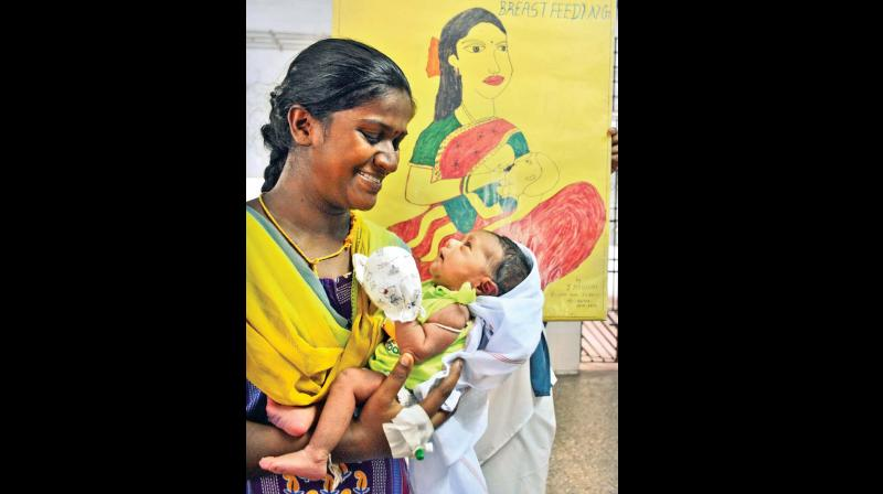 A woman affectionately looks at a newborn girl at Government Kasturba Gandhi Hospital for Women and Children in Triplicane on Thursday.	—DC