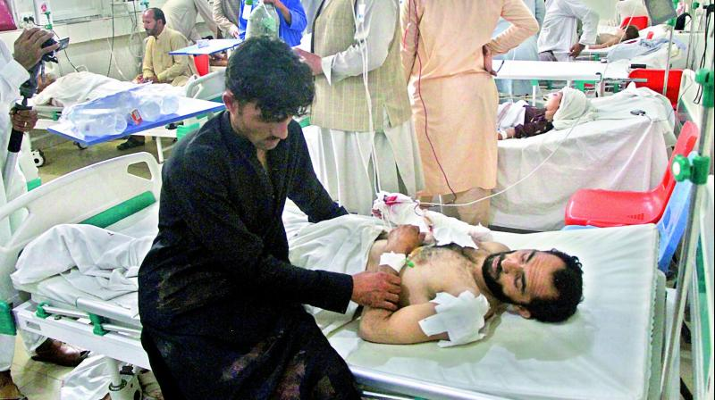 A wounded man receives treatment after the suicide attack in Kabul. 	— AP