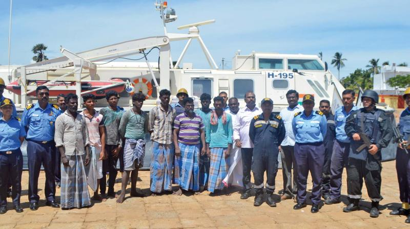 The eight rescued fishermen along with officers  and men of the Indian Coast Guard at the  Mandapam station after the rescue from the Lankan Navy on Friday.—DC
