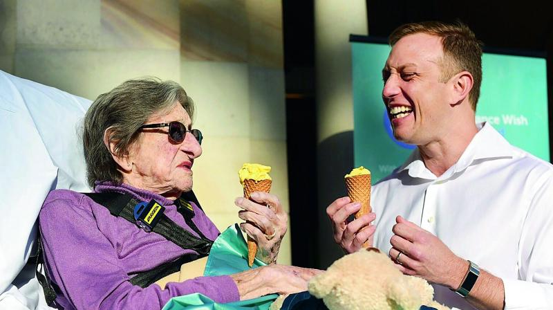 This handout photo taken in Brisbane on Friday shows 92-year-old Betty Dowsett enjoying an ice cream with Queensland Minister for health and ambulance services Steven Miles as she takes the chance to leave palliative care for a few hours to enjoy the sunshine.