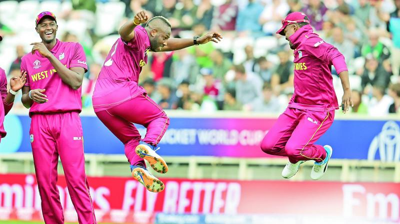 Andre Russell (centre) and Darren Bravo  celebrate a Pakistan wicket as skipper Jason Holder (left) looks on during their World Cup match at Nottingham on Friday. (Photo: AP)