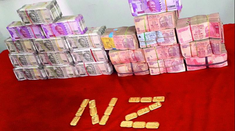Police display the cash and gold seized from various locations in the city on Wednesday.