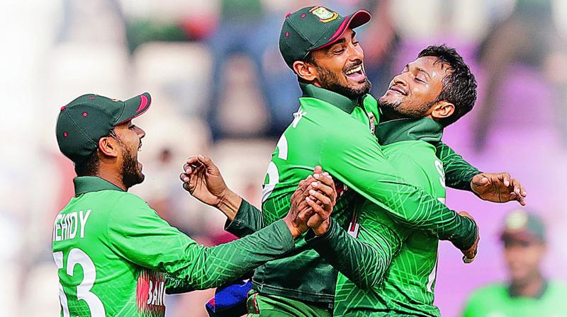 Shakib Al Hasan (right)  celebrates an Afghan  wicket with his teammates. — AFP
