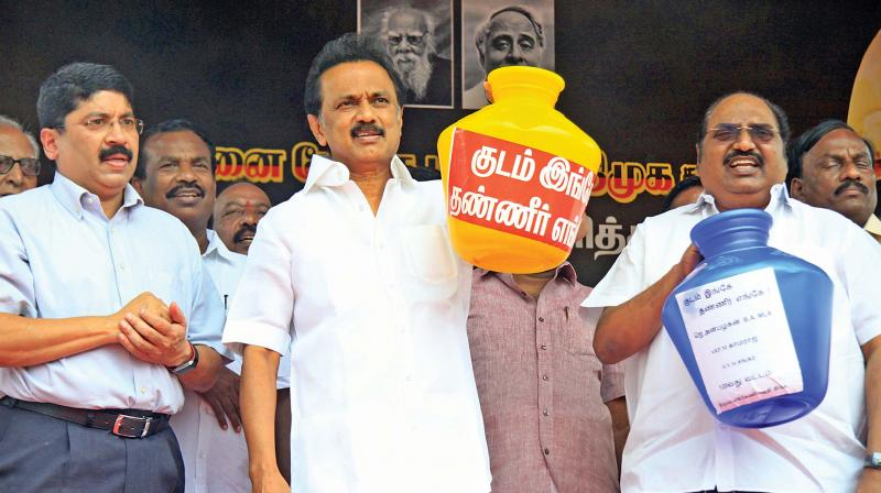 DMK president M.K. Stalin lifts an empty pot to make a point at a protest in Chennai on Monday. Central chennai MP Dayanidhi Maran and Triplicane- Chepauk MLA Anbazhagan are seen.—DC
