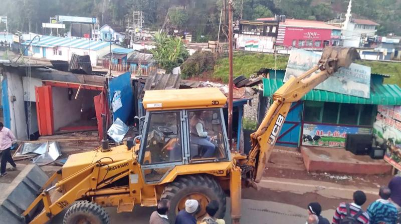 Encroachments on govt land along the water source near bus stand on TDK road in  Coonoor town were removed on Tuesday. —DC