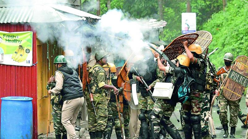 Security personnel fire tear gas during a protest by Gorkha Janmukti Morcha activists in Darjeeling on Saturday. (Photo: PTI)