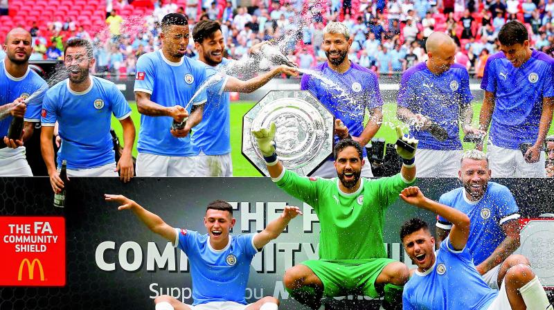 Manchester City players celebrate with the trophy after winning the English FA Community Shield match against Liverpool at Wembley Stadium in London on Sunday. City won 5-4 on penalties.(Photo: AFP)