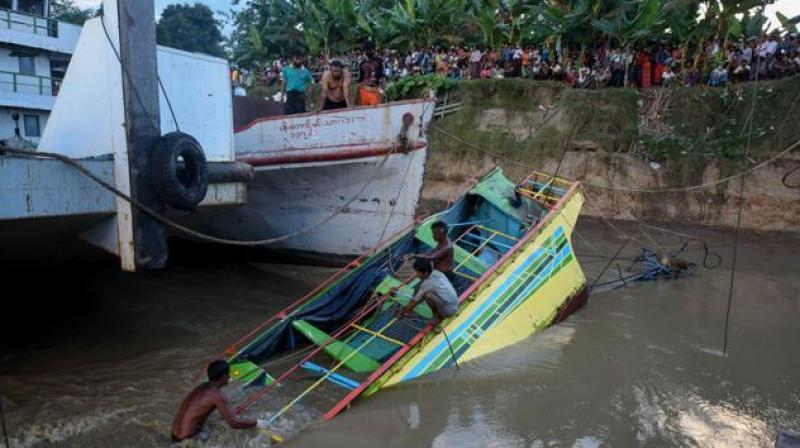 Rescue workers are seen on the sunken ferry partially lifted from the water near the river bank in central Myanmar. The death toll from the ferry disaster four days ago has risen to more than 50, officials said on Wednesday. (Photo: AFP)