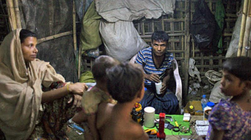 A Rohingya man, woman and children gather in a shop in the Thel-Chaung displacement camp in Sittwe, eastern Myanmar's Rakhine state. (Photo: AFP)