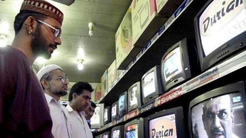 People watch TV programes in Karachi. (Photo: AFP)