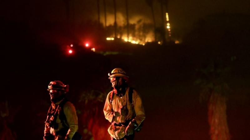 Firefighters battle several intense wind-driven wildfires early on Friday that have swept across densely populated Southern California, destroying at least 500 structures. (Photo: AP)