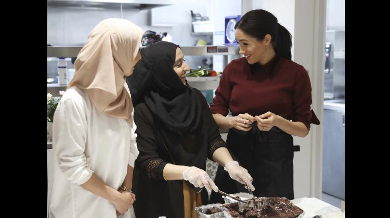 Meghan, Duchess of Sussex, right, talks to people during a visit to the Hubb Community Kitchen to see how funds raised by the 'Together: Our Community' Cookbook are making a difference at Al Manaar in London, Wednesday Nov. 21, 2018. (Photo: AP)