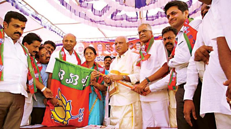 State BJP chief B.S. Yeddyurappa handing over the party flag to former minister H. Nagappa's wife Parimala Nagappa who joined the party at Hanur on Thursday. (Photo: DC)