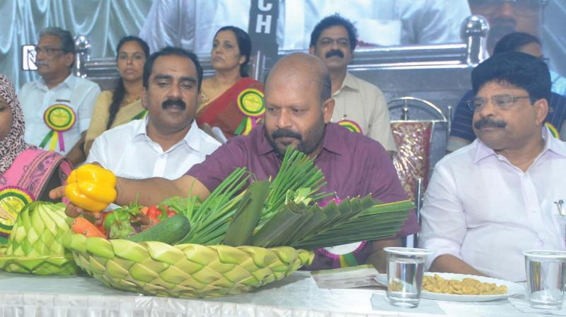 Agriculture minister V.S. Sunilkumar during the inauguration of Njattuvela Chantha at Choornikara panchayat community. (Below): While the city dwellers respond positively to the trend, the scene is different in villages. A woman farmer planting paddy saplings by all herself due to acute shortage of farm labourers at Odannoor region in Palakkad.(Photo: DC)