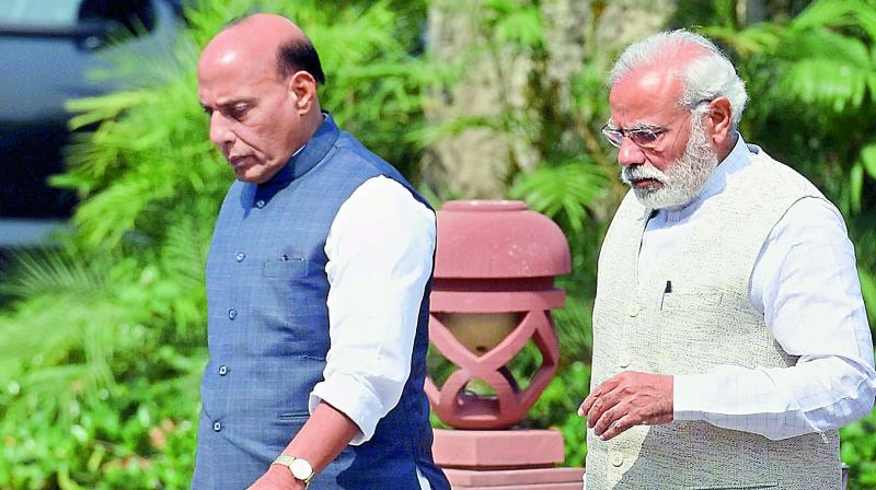 Prime Minister Narendra Modi and Home Minister Rajnath Singh leave after a Cabinet meeting at the Parliament Library in New Delhi on Monday. (Photo: PTI)