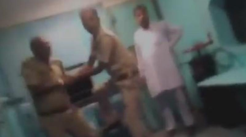 Uttar Pradesh policeman is being thrashed by a Railway Police Force (RPF) jawan while jumping off a train to catch a fleeing prisoner. (Photo: ANI   Screengrab)