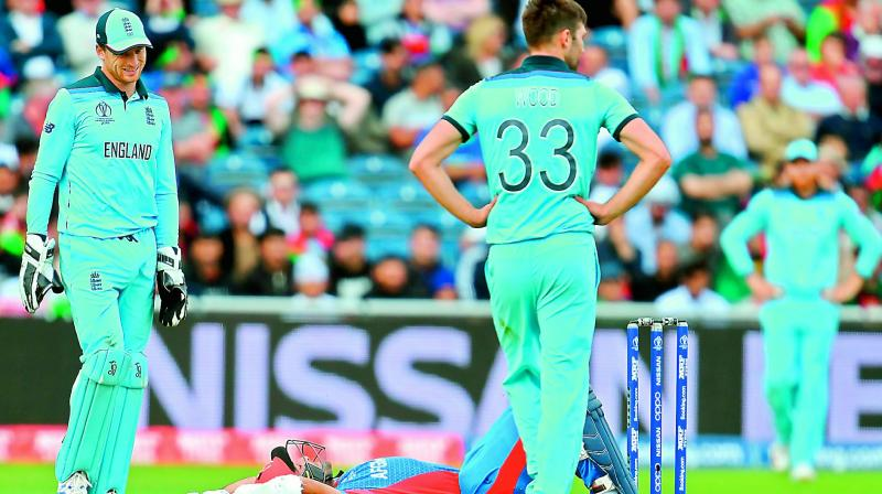Afghanistan's Hashmatullah Shahidi lies on the ground after he was hit by fast bowler Mark Wood's delivery during the match against England at Old Trafford in Manchester on Tuesday. (Photo: AP)